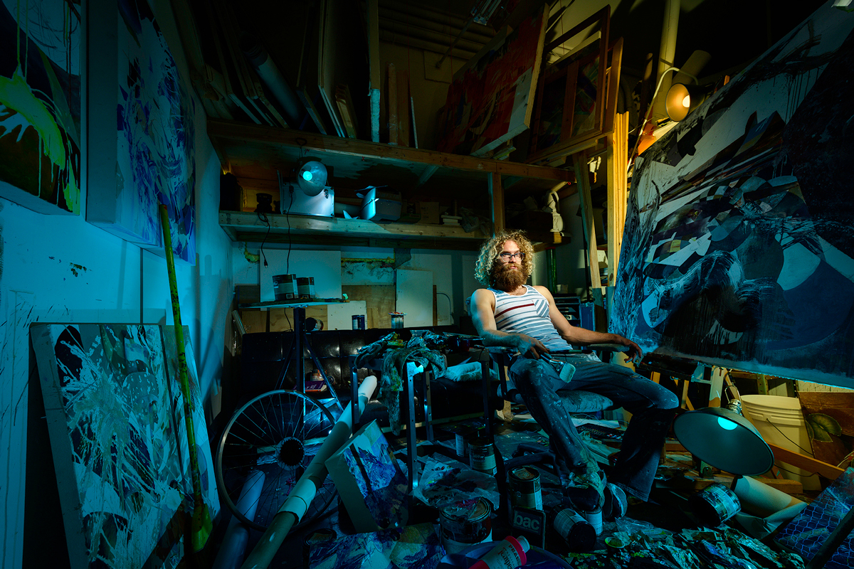 Portrait of an artists in his studio illuminated with saturated blue color.