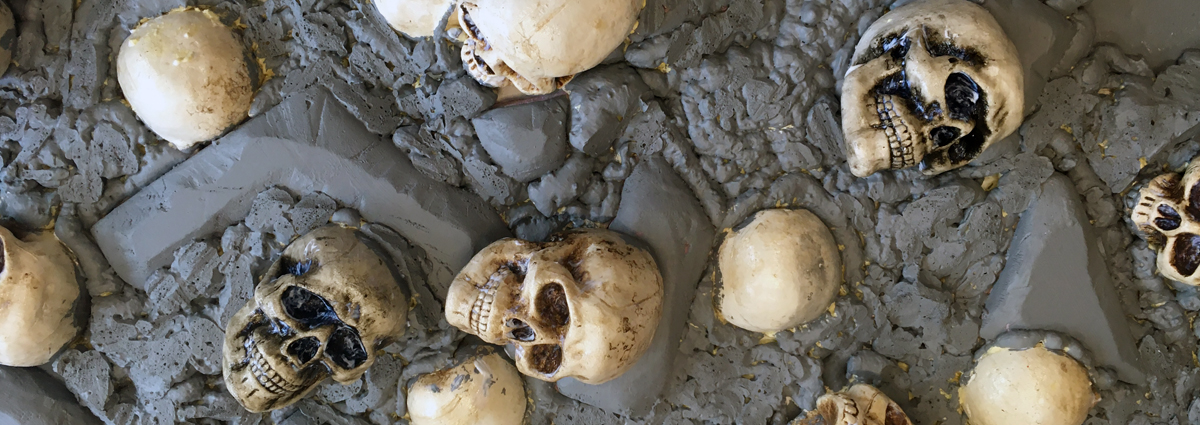 White skulls scattered on grey wall coverage create creepy Halloween scenery.